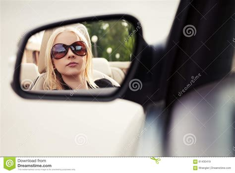 blond woman    car rear view mirror stock