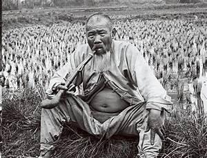 A Guangzhou farmer sitting in his field, smoking, 1900 ...
