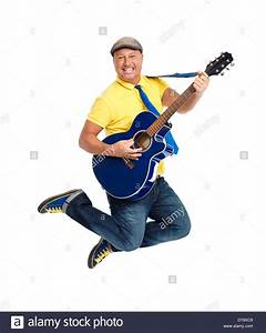 Happy smiling young man guitar player jumping with an ...