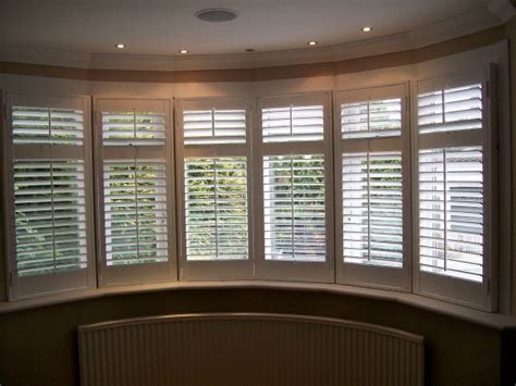 curved bay window shutters painted neutral colours