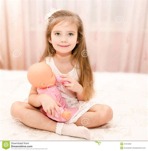 Cute Smiling Little Girl Playing With A Doll Stock Photo