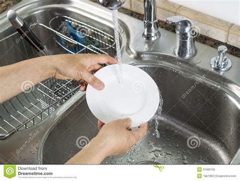 woman hands washing dinner plate  kitchen sink stock