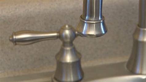 slowly dripping faucet with handle in background stock