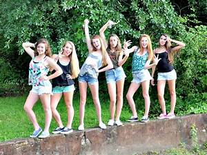 Large group of friends pose on concrete wall. Excellent ...