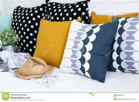 white sofa with colorful pillows colorful pillows on a sofa with white brick wall i royalty