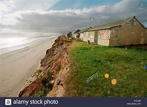 Coastal erosion. Abandoned houses on an unstable cliff ...