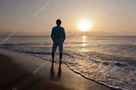 man   beach watching  sunset stock photo