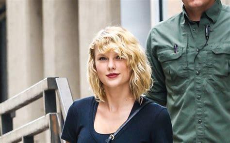 Sorridente e de batom vermelho, Taylor Swift vai a ...