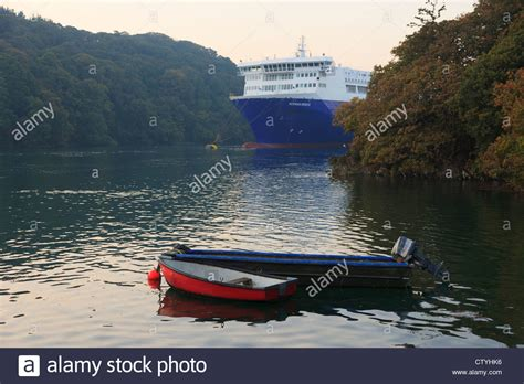 Small Boat On Larger Ship by Small Boats Moored And Large Cargo Ship Laid Up In