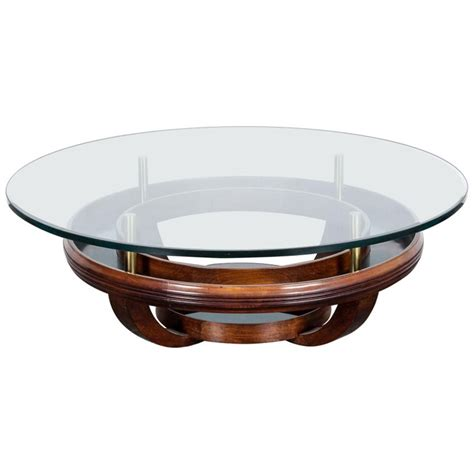 Supported by a sleek, geometric brass base and finished with a mango wood top, this coffee table balances powerful and elegant design. Unique Brazilian Bi-Level Glass Top Round Coffee Table with Wood Base For Sale at 1stdibs