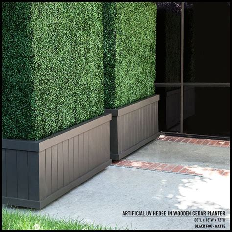 tall artificial hedges  dark brown planters create
