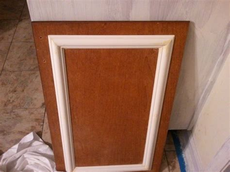 refurbishing kitchen cabinet doors add trim and a new coat of paint to cabinets for a