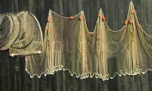 Fishing nets hanging on a wooden house wall | Stock Photo ...
