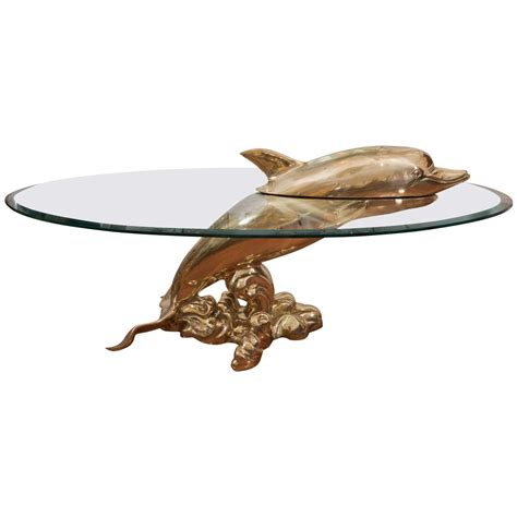 Two dolphins swimming as if in the ocean surround by ocean plants and coral. Dolphin Coffee Table at 1stdibs