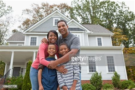 Black Family Standing Together In Front Of House High-Res ...