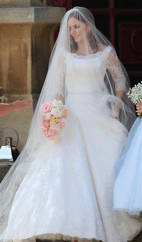 Geri Halliwell is a vision in couture white lace gown and an elegant veil as she kisses new