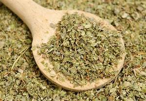 Dried marjoram spice and wood spoon as food background ...