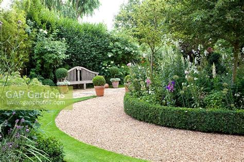 curved garden path gap gardens curved gravel path in country garden edged with low buxus box hedge image no