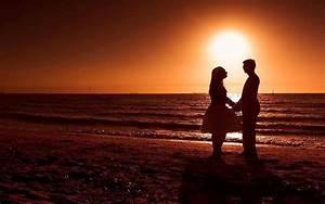 Pareja romántica en la playa durante la puesta del sol ...
