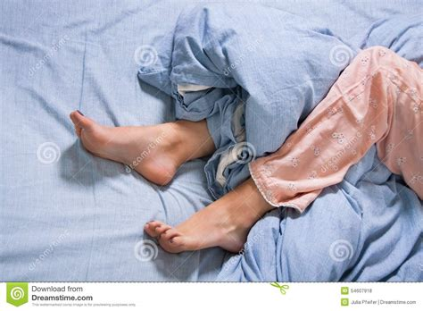 bare feet   young woman  blue bed stock photo image