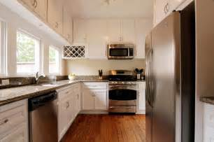 classic and antique white kitchen cabinets with stainless steel appliances and brown wooden