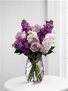 Purple flowers and pink flowers arranged in a purple vase ...