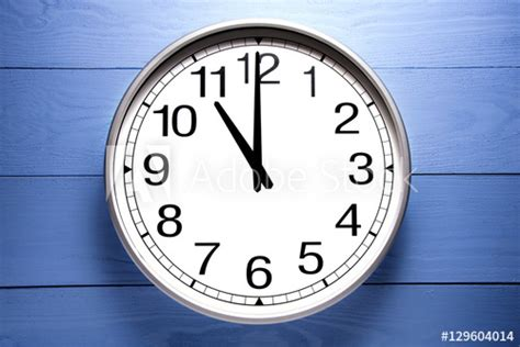 Round Clock Shows Shows At 11 O'clock, Clock On Blue