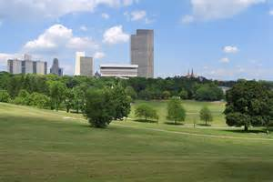 a green space with trees and rolling lawns is flanked by modern style buildings in the