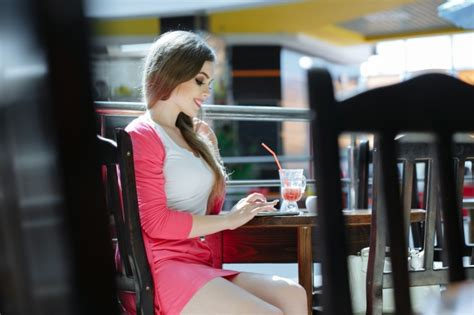 Girl Typing On Her Phone While Sipping A Soda Photo
