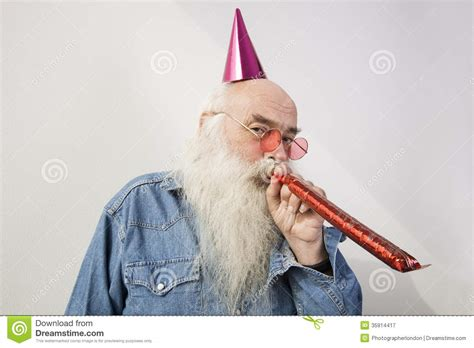 Portrait Of Senior Man Wearing Party Hat While Blowing