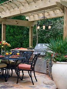 outdoor kitchen and dining area with rustic wood pergola