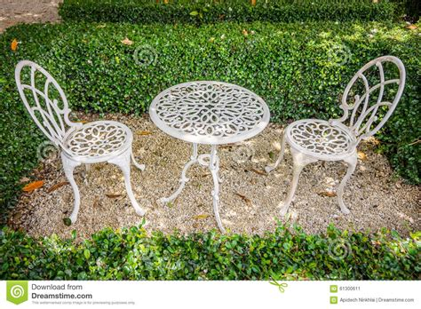 vintage white metal table and chairs in garden stock photo
