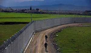 A Turkish army officer patrols a wall under construction ...