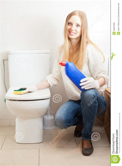 Happy Long haired Woman Cleaning Toilet Bowl At Home Stock