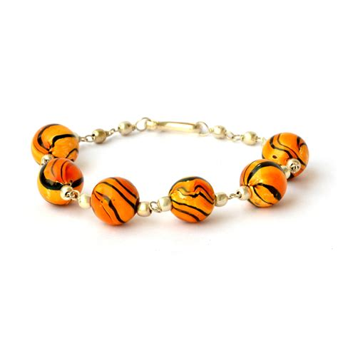 Handmade Bracelet Having Orange Beads With Black Stripes. Handmade Silver Jewelry. Emerald Bands. Portuguese Watches. Therapy Bracelet. Gaelic Engagement Rings. Elegant Watches. Bridesmaid Jewelry. Crown Pendant
