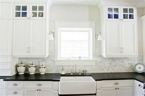 black counter farmhouse sink marble subway tile backsplash