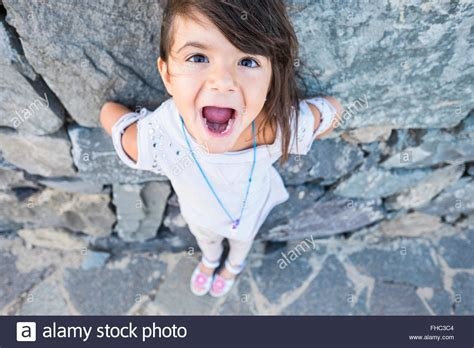 Portrait of little girl with mouth open in front of a rock