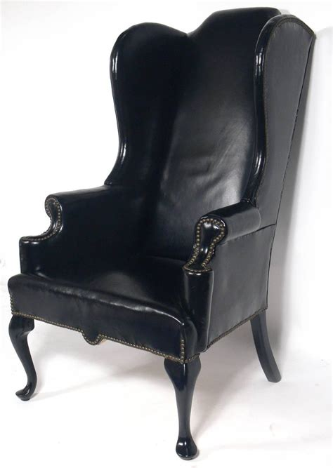 perfectly patinated black leather wing chair for sale at