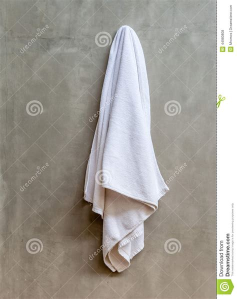 hanging white towel draped on exposed concrete wall in the