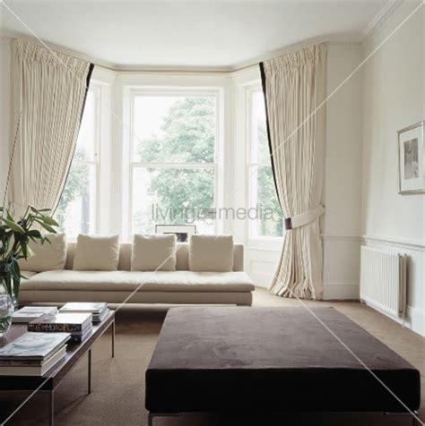 gardinen wohnzimmer modern cremefarbenes sofa und vorhänge vor dem erkerfenster in einem weissen zeitgenössischen