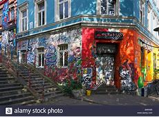 Graffiti and wall art cover a shop and apartments in the