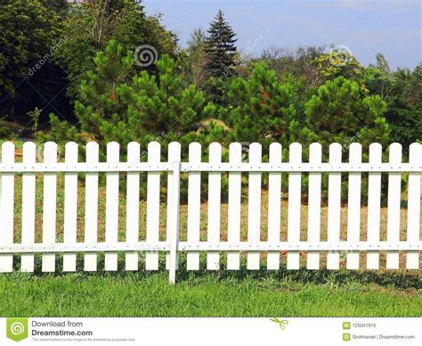 white wooden fence on green grass against of the trees