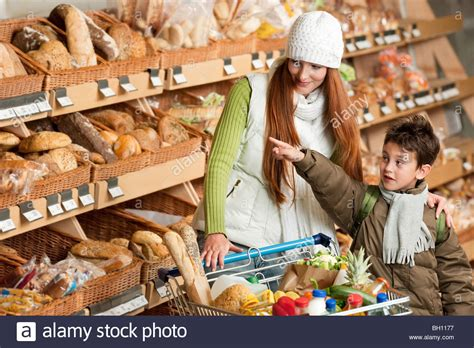 Grocery store shopping: Young woman with child buying ...