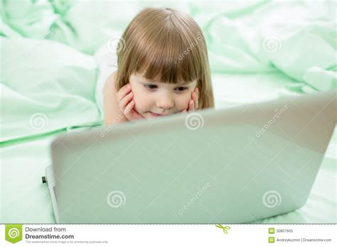 Serious Kid Girl Lying On Bed With Notebook Stock Image