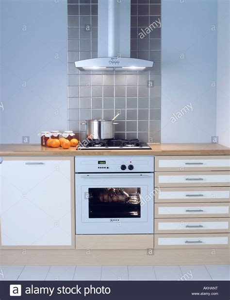 wood kitchen island cart extractor fan above white oven in modern white kitchen