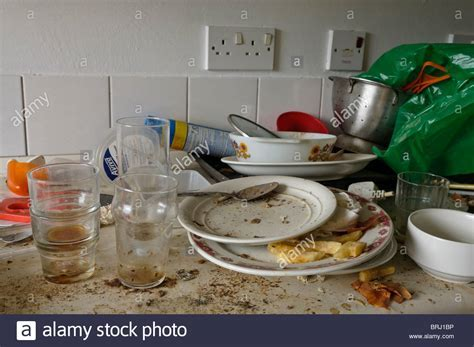 Very dirty dishes on a dirty kitchen worktop Stock Photo