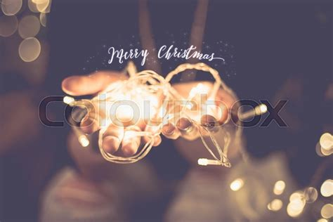 merry christmas glowing word over with party light string bokeh in vintage filter holiday