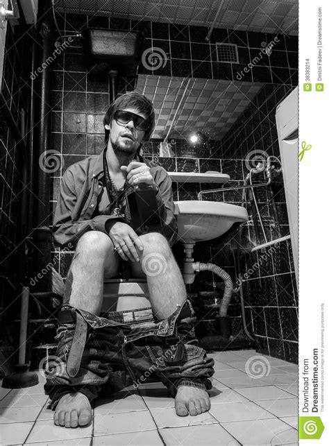 drunk man sits   toilet   bottle  whiskey stock