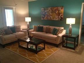 teal and yellow living room with sectional sofa and white coffee table teal brown and gold