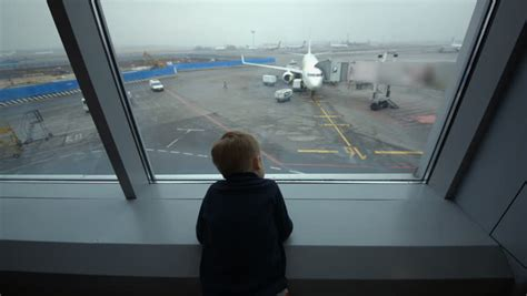 Little Boy Looking Out The Window Of The Airport Terminal